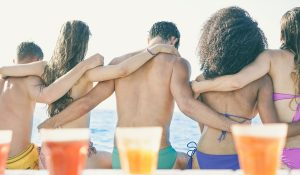 Back view of young friends sitting on boat in summer vacation - Group of people enjoying holidays together traveling around the sea - Friendship, bonding, fun, youth, travel concept - Retro filter
